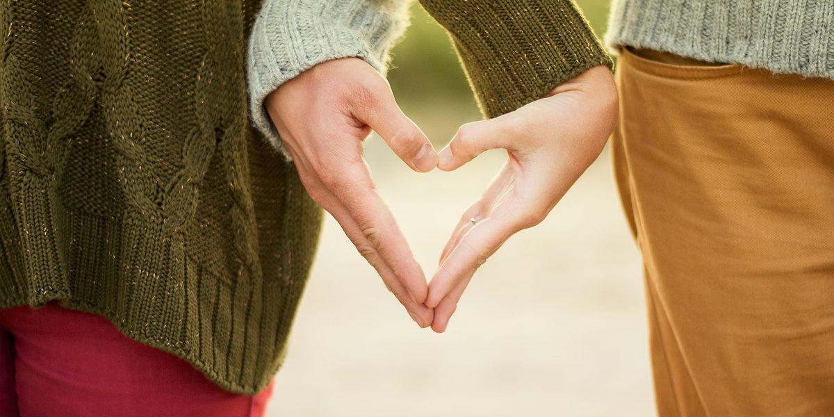 To personer former et hjerte med hendene. Foto.