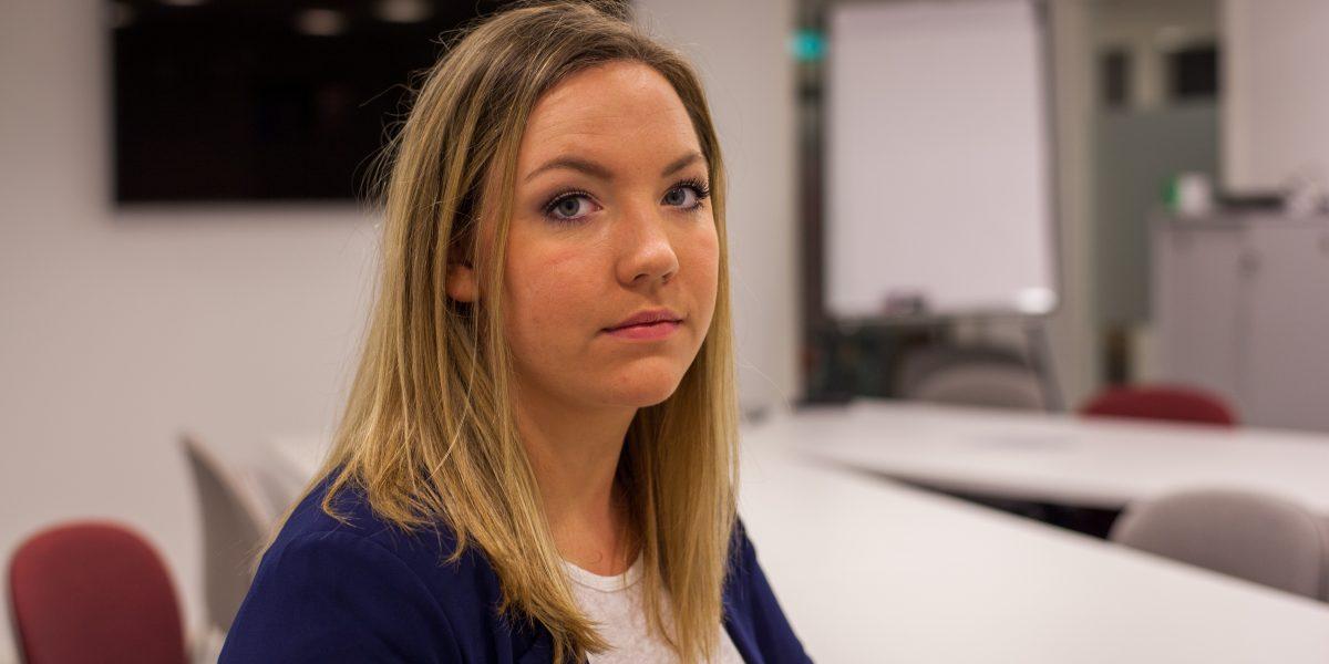 Styreleder Camilla Lyngen sitter i et møterom og ser alvorlig i kamera. Foto.