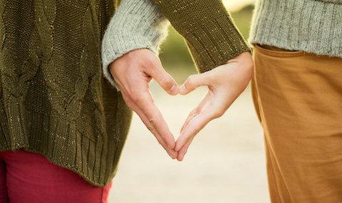 To personer former hendene sine til et hjerte. Foto.