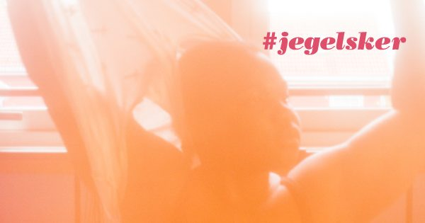Kvinne sitter i en seng og strekker armene over hodet. Teksten #jegelsker står på bildet. Foto.