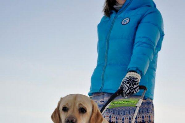 Kvinne holder førerhund. Foto.