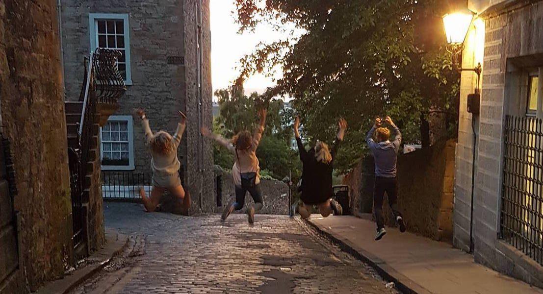 Fire personer hopper i en brosteinsbelagt gate på kveldstid. Foto.