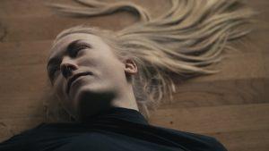 En kvinne ligger på gulvet. Foto.