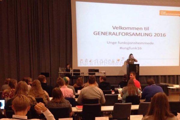 En kvinne står foran en forsamling. I bakgrunnen er det en powerpointpresentasjon. Foto.