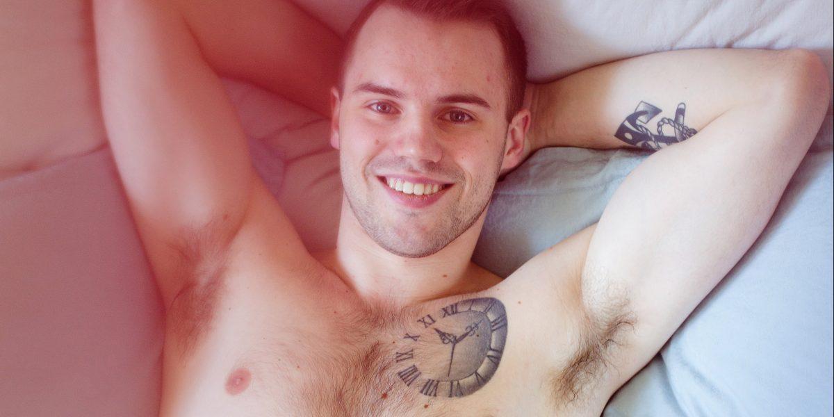 En mann ligger i en seng med armene bak hodet og smiler til kamera. Han har bare boksershorts på. Foto.