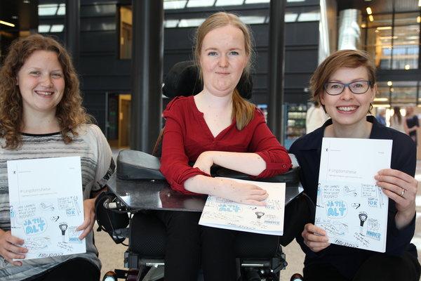 Tre kvinner holder fram den nye ungdomshelsestrategien. Foto.