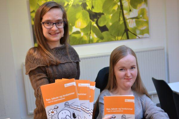 To kvinner smiler til kamera, mens de holder fram eksemplarer av en brosjyre. Foto.