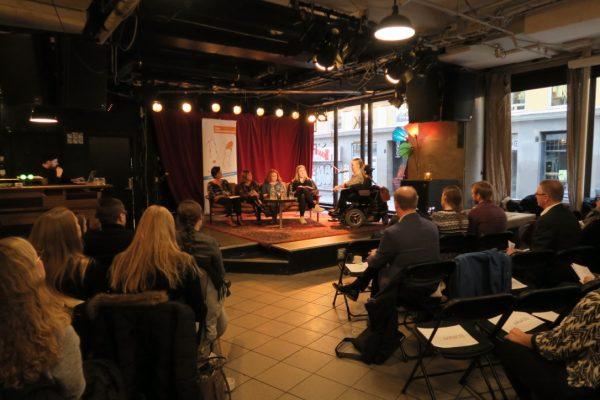 Et publikum sitter foran en scene der det foregår en debatt. Foto.