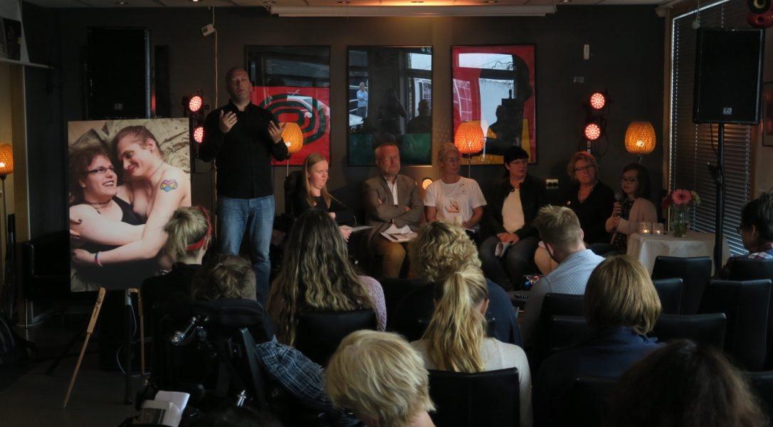 En gruppe publikummere sitter på stoler og lytter til en paneldebatt på en scene. Der står også en tegnspråktolk. I tillegg er det et foto av et par i omfavnelse til venstre for scenen. Foto.