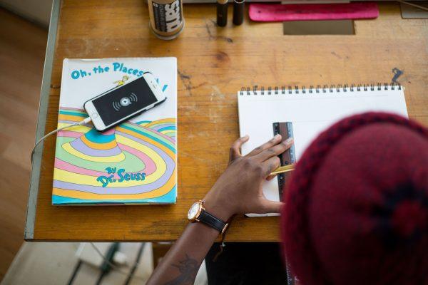 En person sitter ved en pult og arbeider eller studerer. Foto.