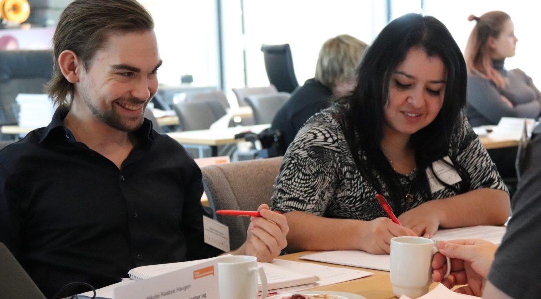 En mann og en kvinne sitter ved et bordt og snakker sammen. På bordet ligger dokumenter og kaffikopper. Foto.