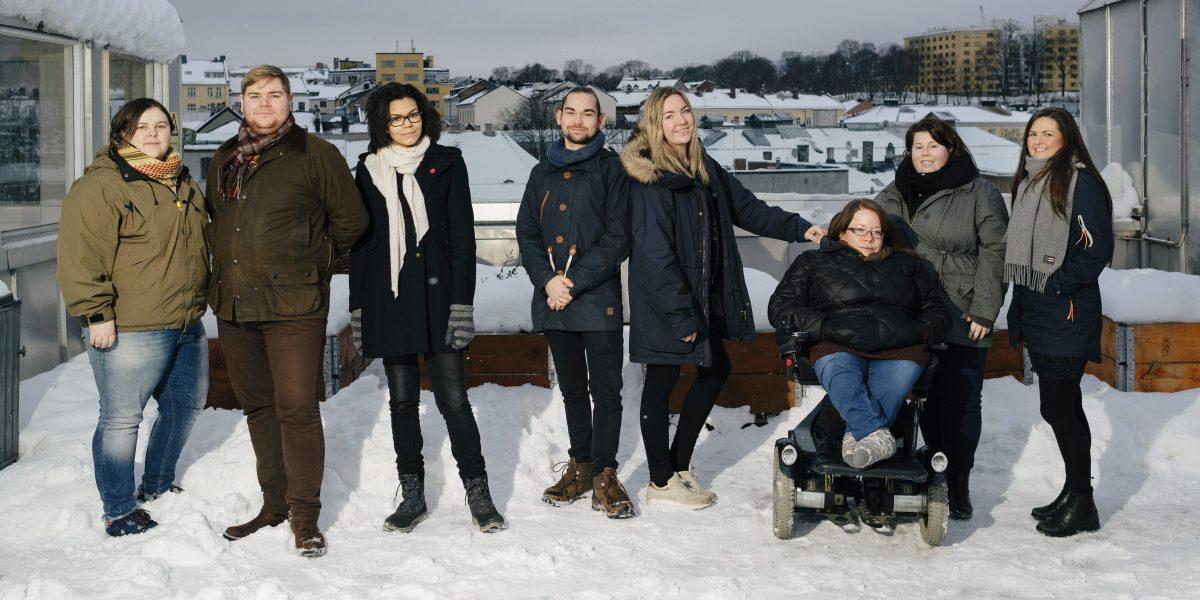 Åtte personer står på en takterrasse med Oslo by i bakgrunnen. Det er snø og overskuet vær. De ser i kamera. Foto.