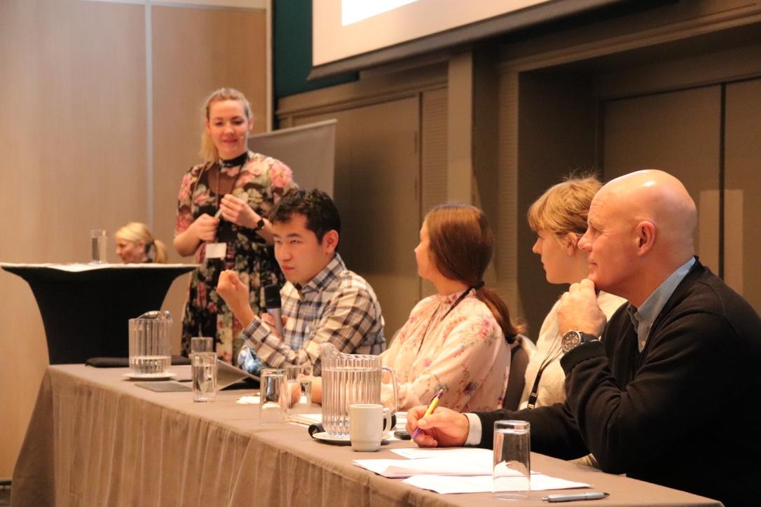 Fem personer sitter i et panel. Foto.