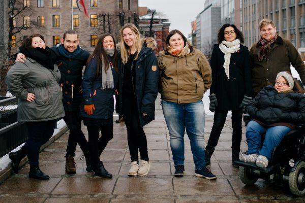 Åtte personer smiler til kamera. Poserer foran regjeringskvartalet. Foto.