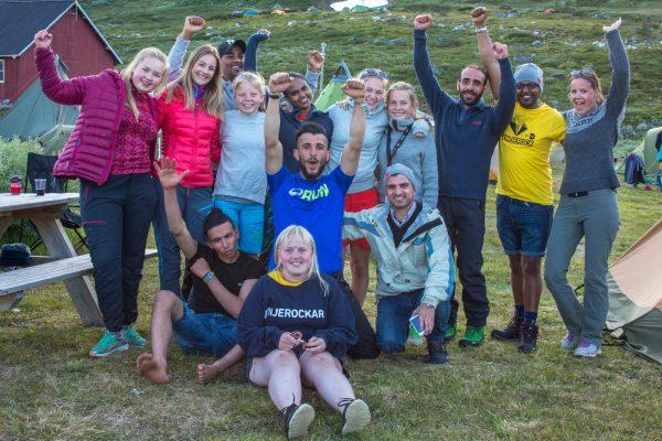 En gruppe mennesker smiler og jubler. De er på fjellet. Foto.