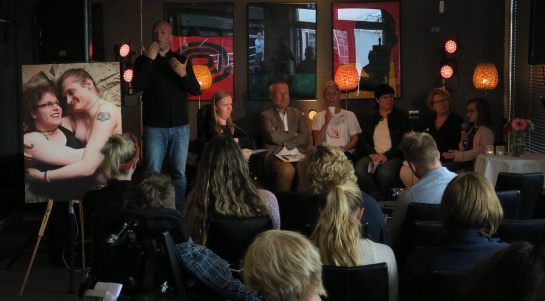 Personer på en scene i debatt, og mennesker i publikum foran. Foto.