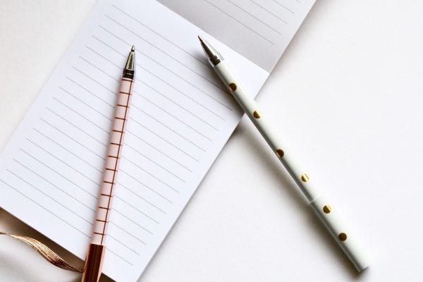 To blyanter ligger på en skriveblokk. Foto.