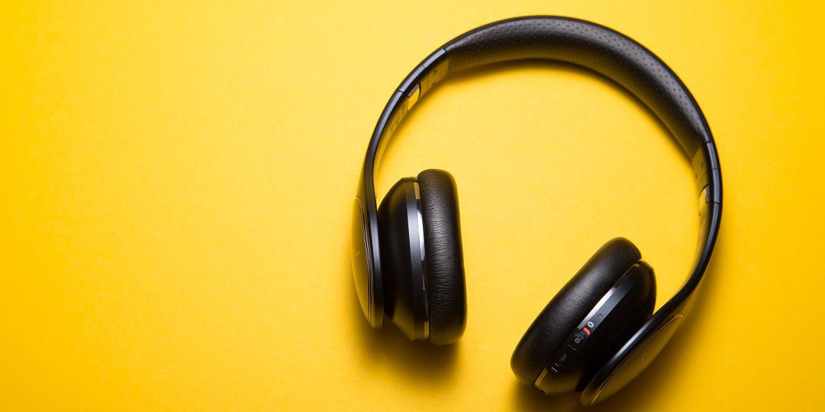 Høretelefoner ligger på en gul bakgrunn. Foto: Malthe Wingen/Unsplash