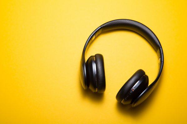 Høretelefoner ligger på en gul bakgrunn. Foto.