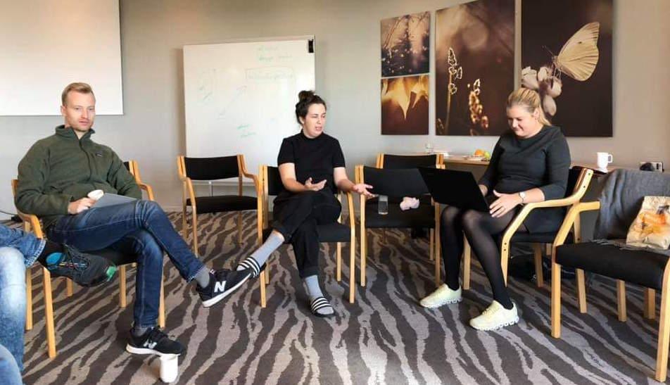 Tre personer sitter på stoler i en sirkel. De diskuterer og noterer på en PC. Foto.