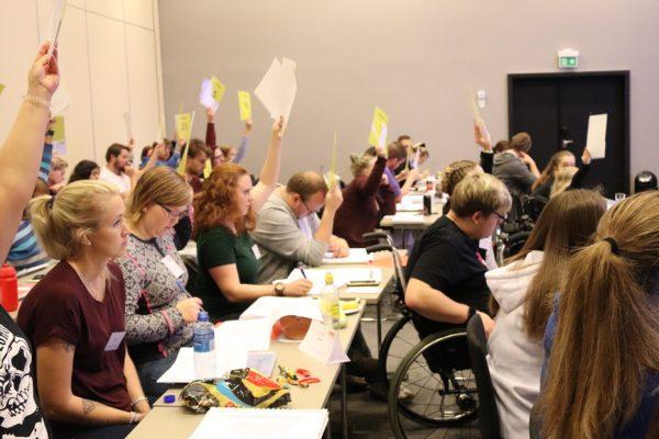 Personer rekker delegatskilt i været for å stemme.