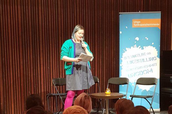 Kvinne står på scene og leser dikt foran et publikum.