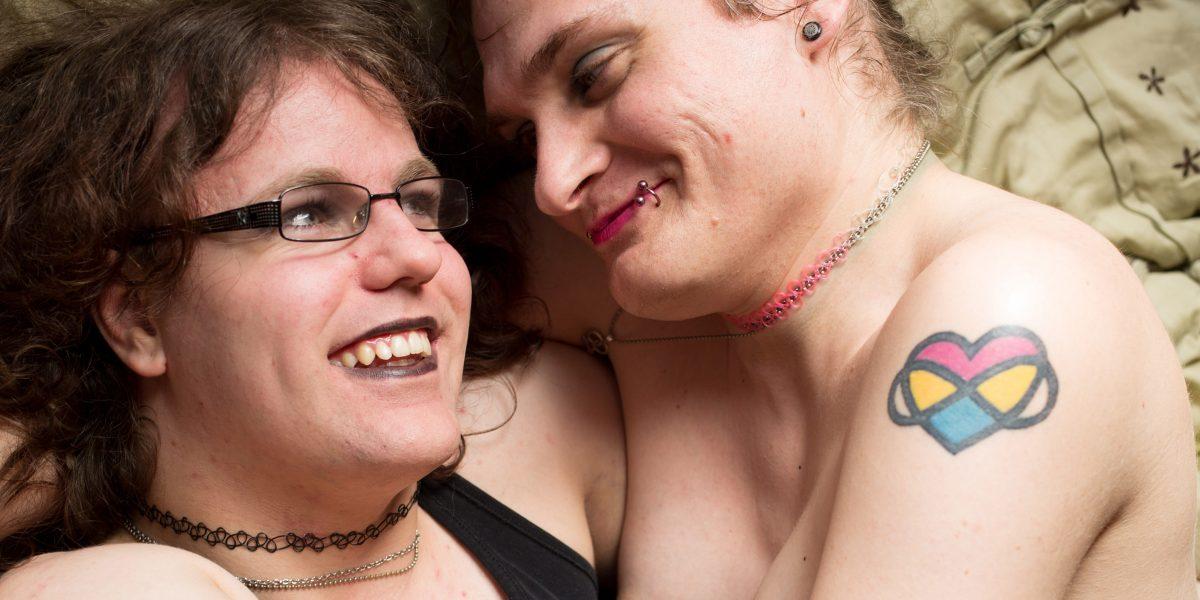 Et kjærestepar i omfavnelse på en seng. Foto.