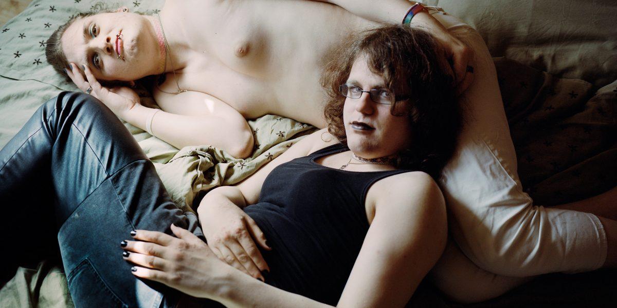 Et kjærestepar ligger på en seng og ser i kamera. Foto.