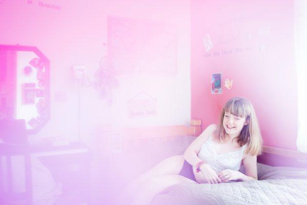 Kvinne ligger i henslengt i en seng og smiler. Hun har på seg en singlet og truse, og det er et rosa slør over bildet. Foto.