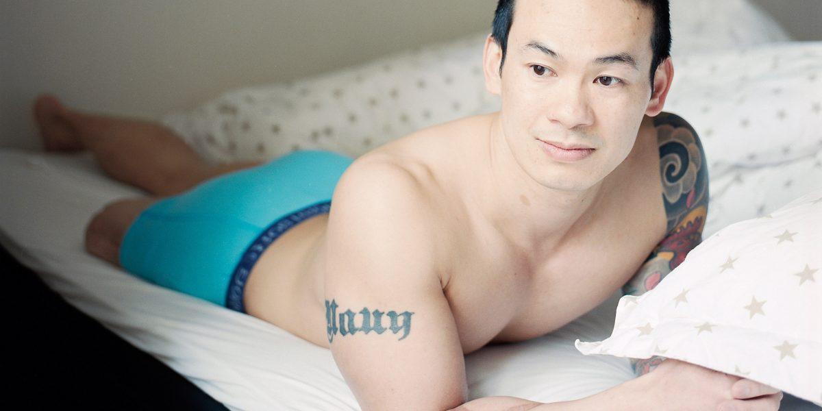 Mann ligger i en seng og ser mot kamera. Han har på seg bokser. Foto.