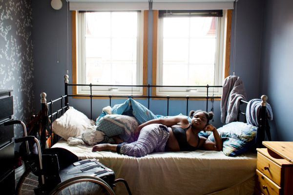 Kvinne ligger i en seng og ser mot kamera. Foto.