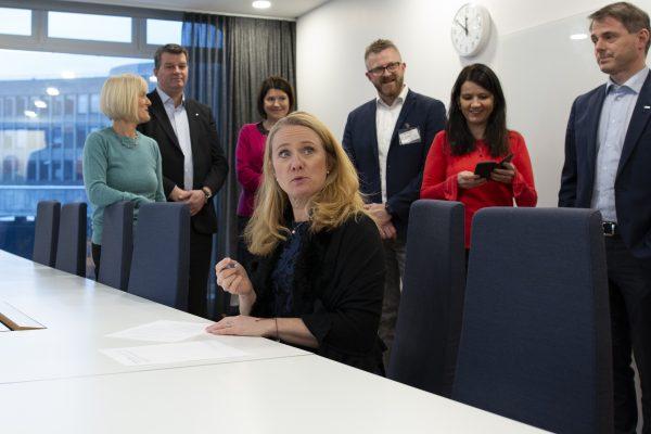Kvinne signerer mens en gruppe ser på. Foto.