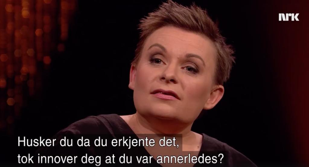 """En kvinne ser i kamera. Foran henne er teksten """"Husker du når du anerkjente at du var annerledes?"""". Skjermdump fra NRK."""