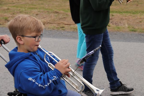 Gutt spiller trompet sittende