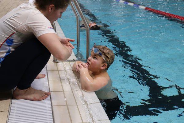 En gutt i svømmebasseng får tips fra instruktør