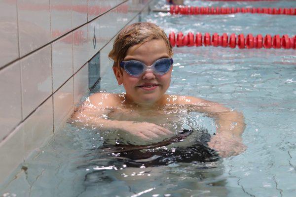 En gutt smiler i et svømmebasseng
