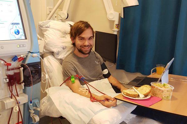 Ung mann sitter i sykehus seng