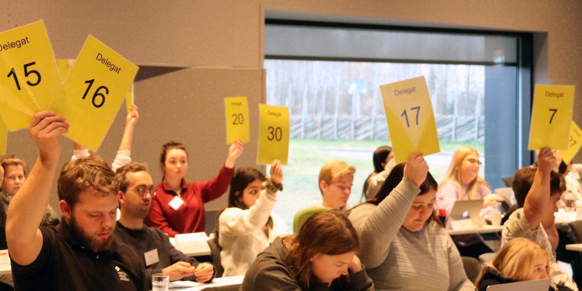 Delegater på Generalforsamlingen holder opp skilt for å stemme