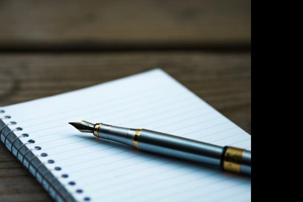 En penn ligger på en notisblokk