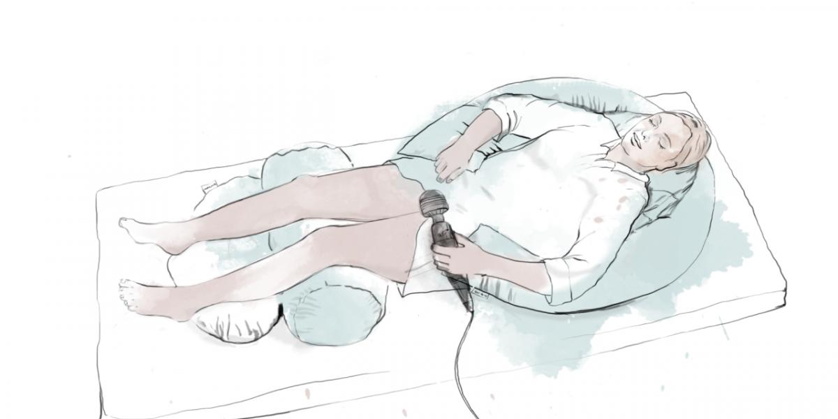 En ung kvinne ligger i en seng med støtteputer og en vibrator.