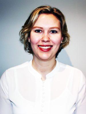 En kvinne i hvit skjorte smiler til kamera.