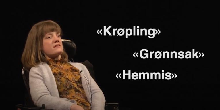 En kvinne i rullestol med skjellsord skrevet på skjermen ved siden av henne