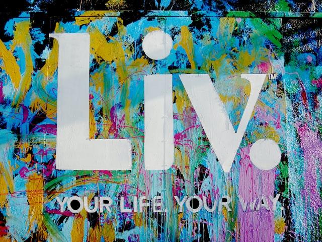 Foto av George Pagan III, Unsplash. En fargerik bakgrunn hvor det står Liv. your life your life your way (lev livet ditt på din måte).