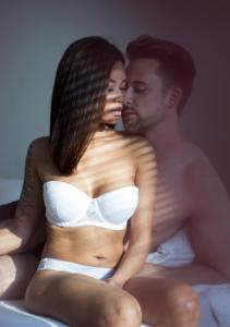 En kvinne i undertøy sitter på en seng med en avkledd mann.