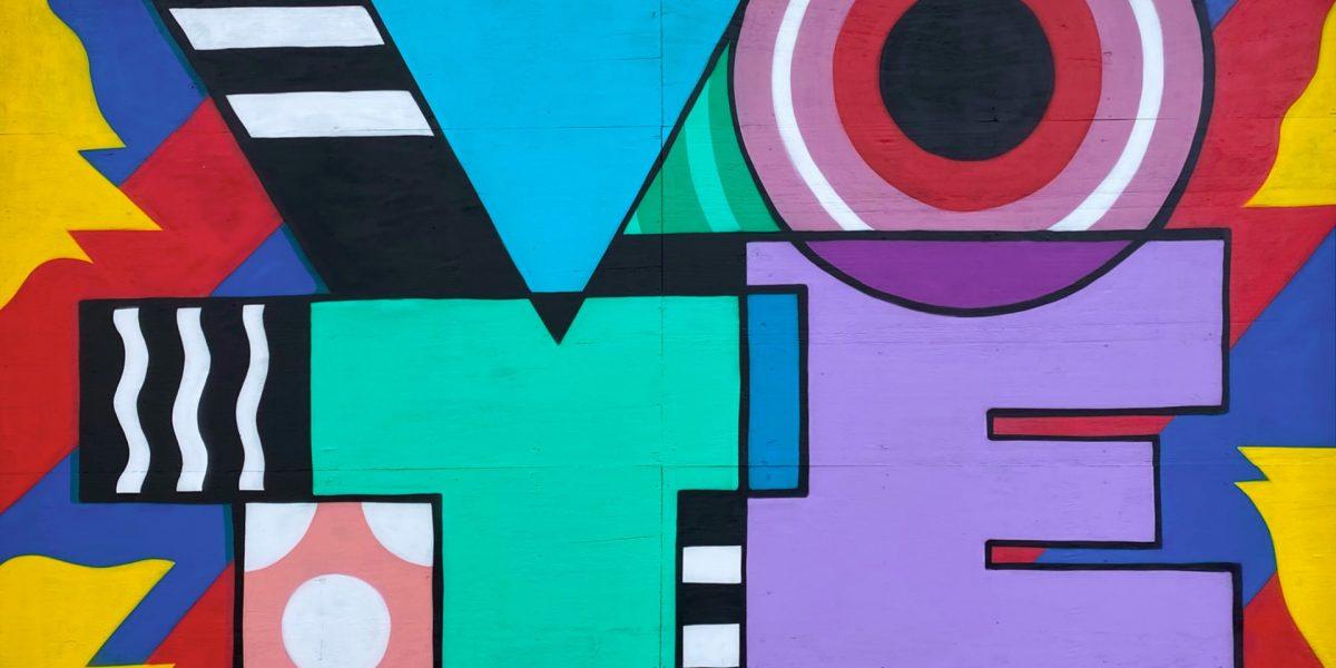 Vote i fargerike blokkbokstaver på en vegg